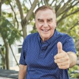 Portrait of excited senior man smiling and showing thumbs-up